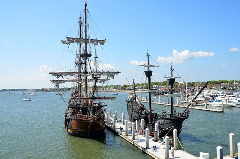 Galleons at a dock.